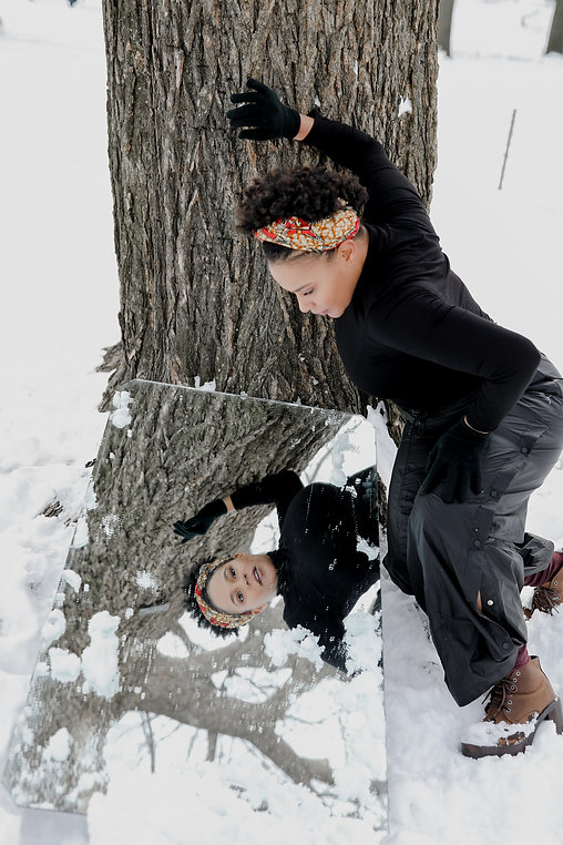 Destini Rogers, a short haired black woman, wears a colorful headband and leans on a tree in the snow. She looks into a mirror on the ground so her reflection is looking directly at the camera.