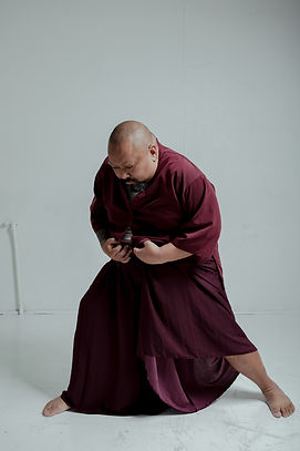 Mike Esperanza stands hunched over in a maroon shirt and maroon floor-length skirt looking pensively at the floor.