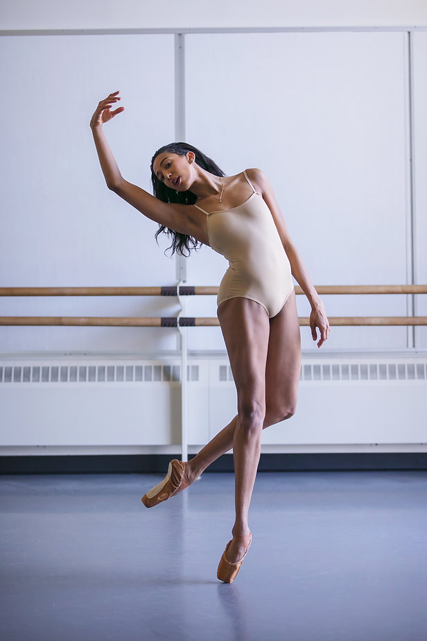 Amanda Morgan in a tan leotard dancing en pointe in a dance studio with her arm over her head.