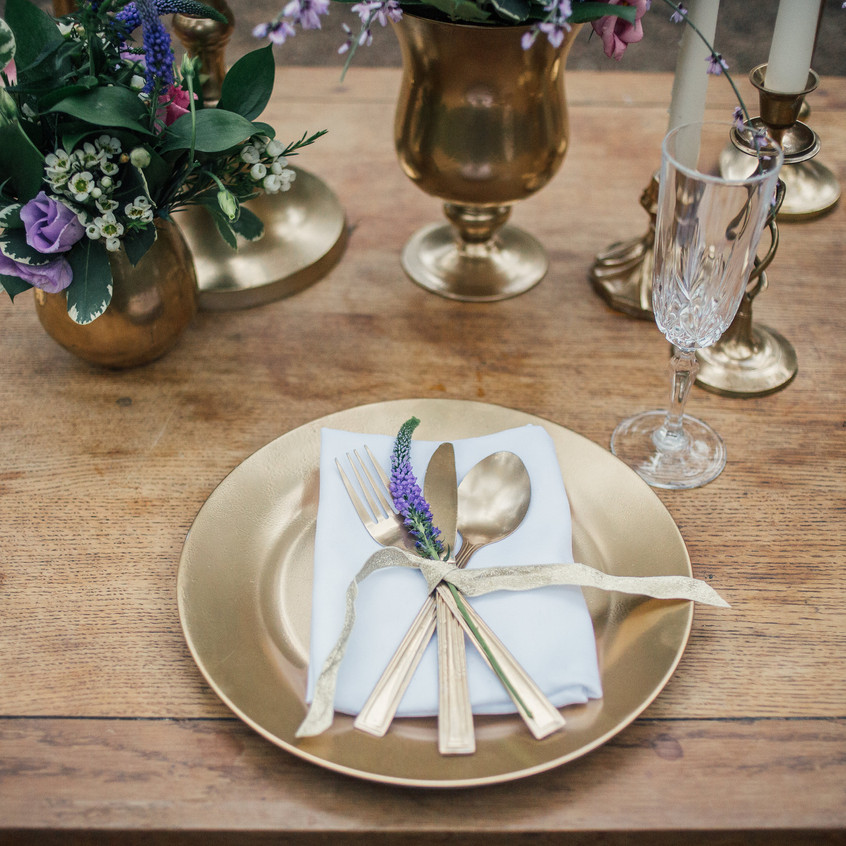 Gold cutlery on charger plate