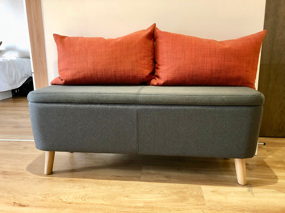 Grey storage ottoman with orange pillows from the sofa