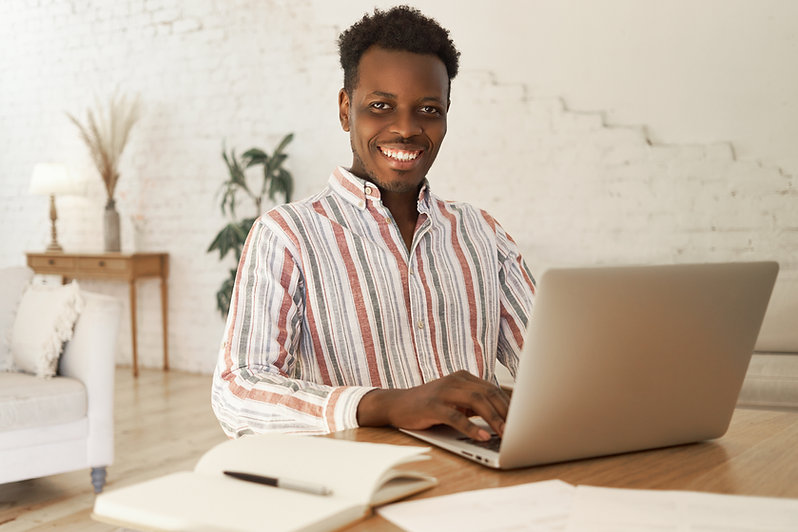 cheerful-young-african-student-sitting-t