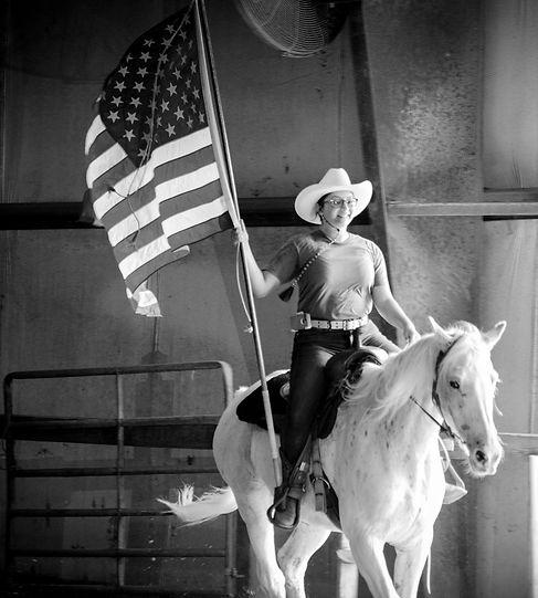 Adriana Lynn Photographer riding a horse with the america flag