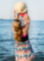 A mother throws her daughter above her head while playing on the beach in yorktown virginia.