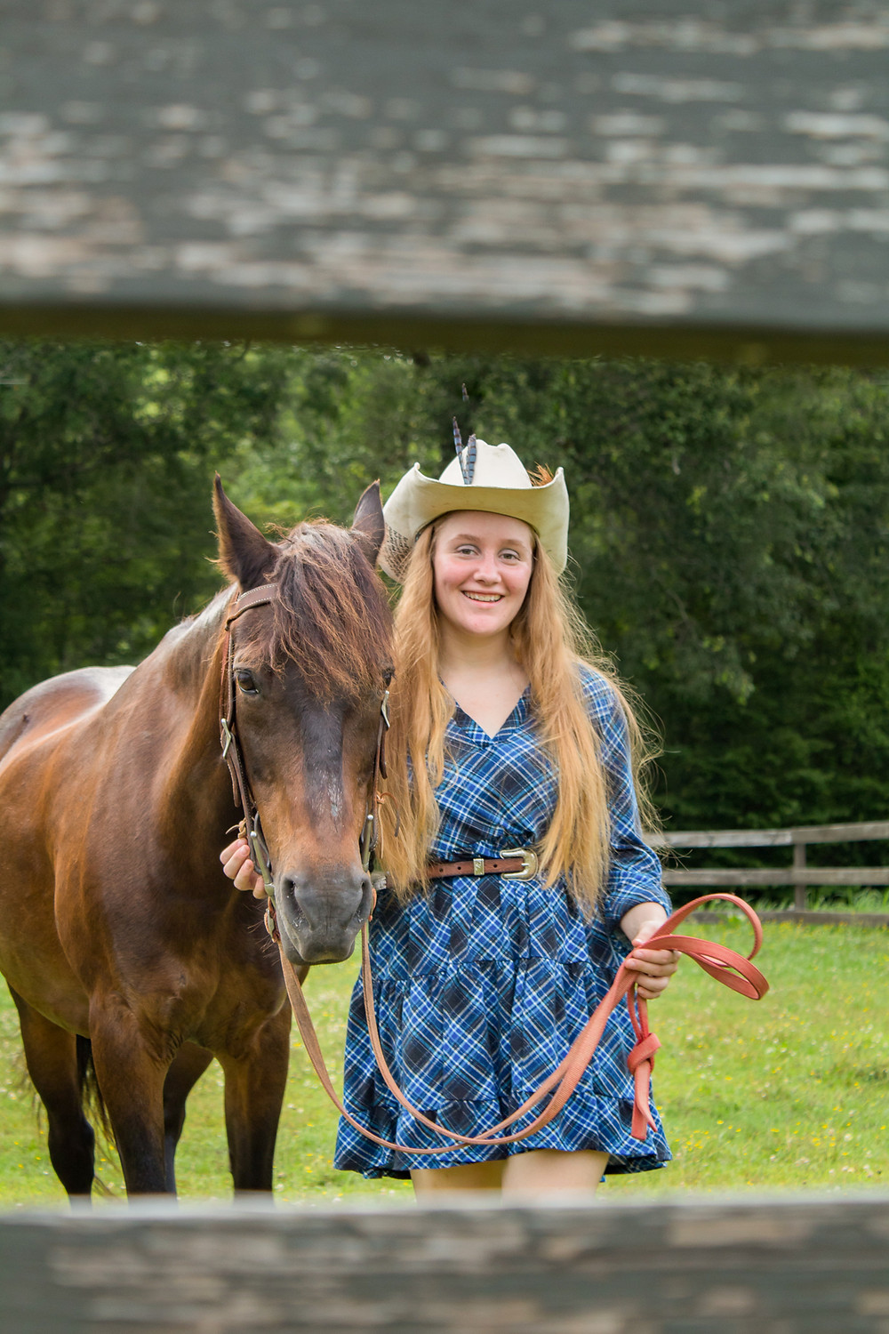 A high school senior posing with her favorite horse at a summer camp
