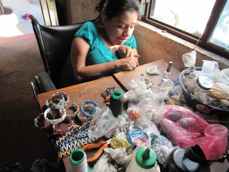 Francisca makes earrings and bracelets out of recycled magazine paper and wire.