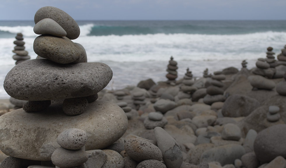 piles of rock cairns at the beach