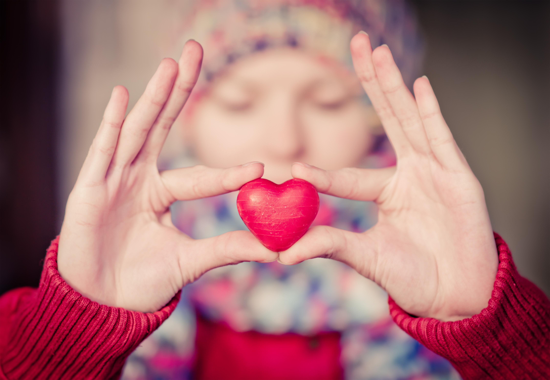 Heart shape love symbol in woman hands w
