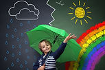 Child holding an umbrella standing in fr
