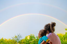 Mom with a child looks at the rainbow. M