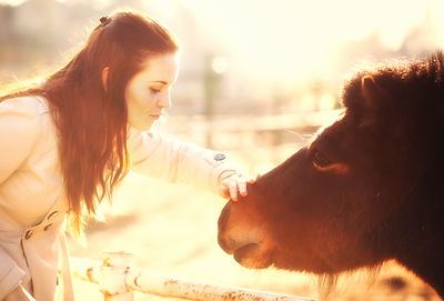 Young woman stroking pony in mini zoo, l