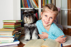 girl and her dog in glasses reading a bo