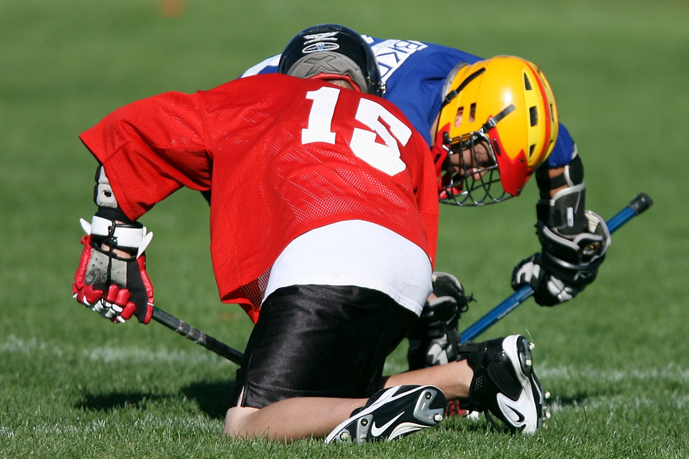 2 lacrosse players tackling each other