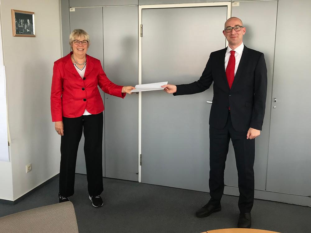 Dirk Woschei übergibt der amtierenden Bürgerneisterin Hansen seine Bewerbungsunterlagen für das Bürgermeisteramt Uetersen