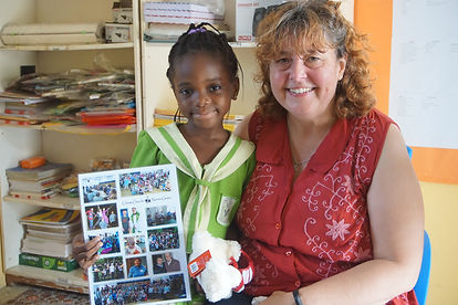 smiling child holds up a photo montage and fluffy toy next to a women wearing a red top