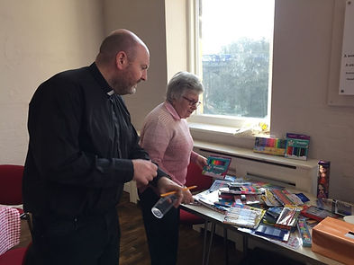 a vicar and a women arrange stationery on a table in a church hall