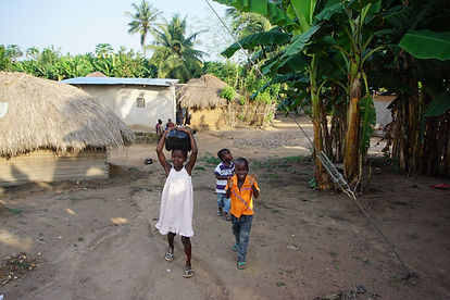 three laughing children walking under a tree next to mud houses