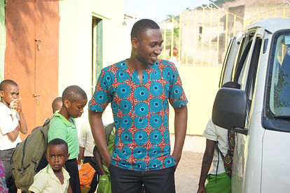 smiling man helping children get into a schoolbus
