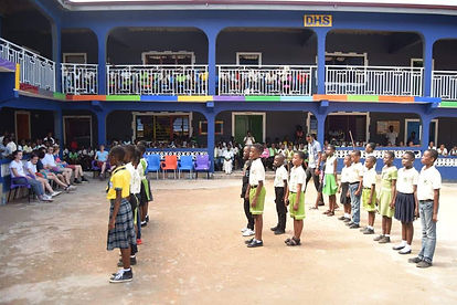 rows of children in lines on a playground in front of a colourfully painted school