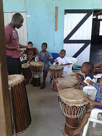 Musical Director, Corey Bradshaw, teaches new young students how to play the drums.