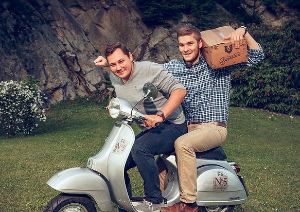 Martin Paul und Lukas Renz sitzen am Moped und fahrenlos. Lukas Renz trägt auf seiner Schulter ene Kiste Bärnsein.