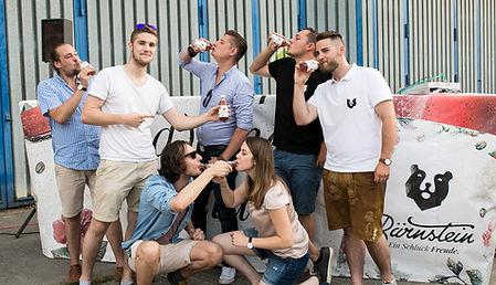 Junge Menschen stehen beisammen und trinken Bärnstein.
