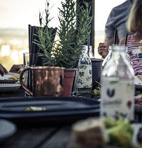 Abbildung eines Tisches, auf dem Flasche Bärnstein und Rosmarin stehen.