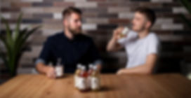Junge Männer sitzen im Büro und trinken Bärnstein