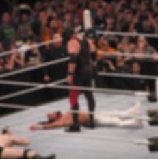 Kane standing over WWE World Heavyweight Champion Seth Rollins at 2015 Night of Champions at the Toyota Center in Houston, TX