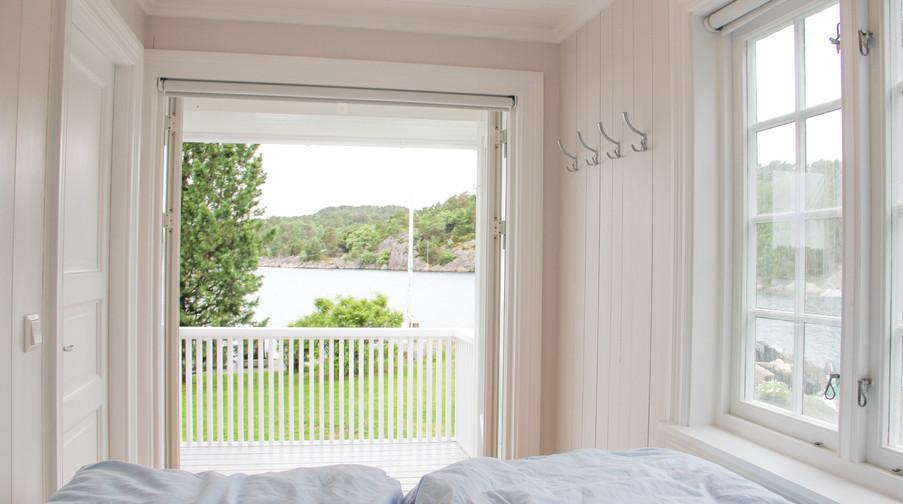 Det ene av to soverom i annekset med opphøyd dobbeltseng med sjøutsikt. Gjelder begge rom.