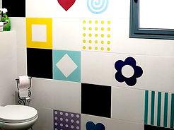 דוגמאות גרפיות גדולות וצבעוניות על קיר בחדר רחצה בשדה-אליעזר