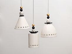שלוש מנורות בצורות שונות - שחור, טבעי וזהב בפינת אוכל ברעננה