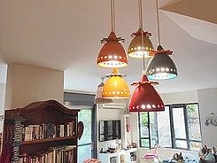 חמש מנורות צבעוניות מקרמיקה מעל שולחן אוכל עגול בזיכרון-יעקב