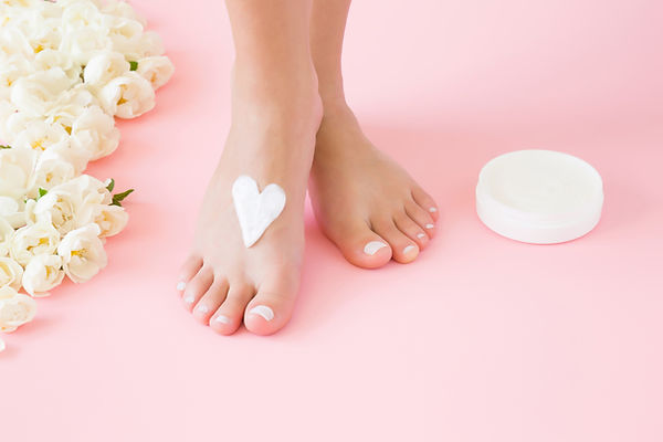 Woman's perfect, groomed feet with jar o