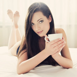 Cheerful Young Woman Relaxing in Bed