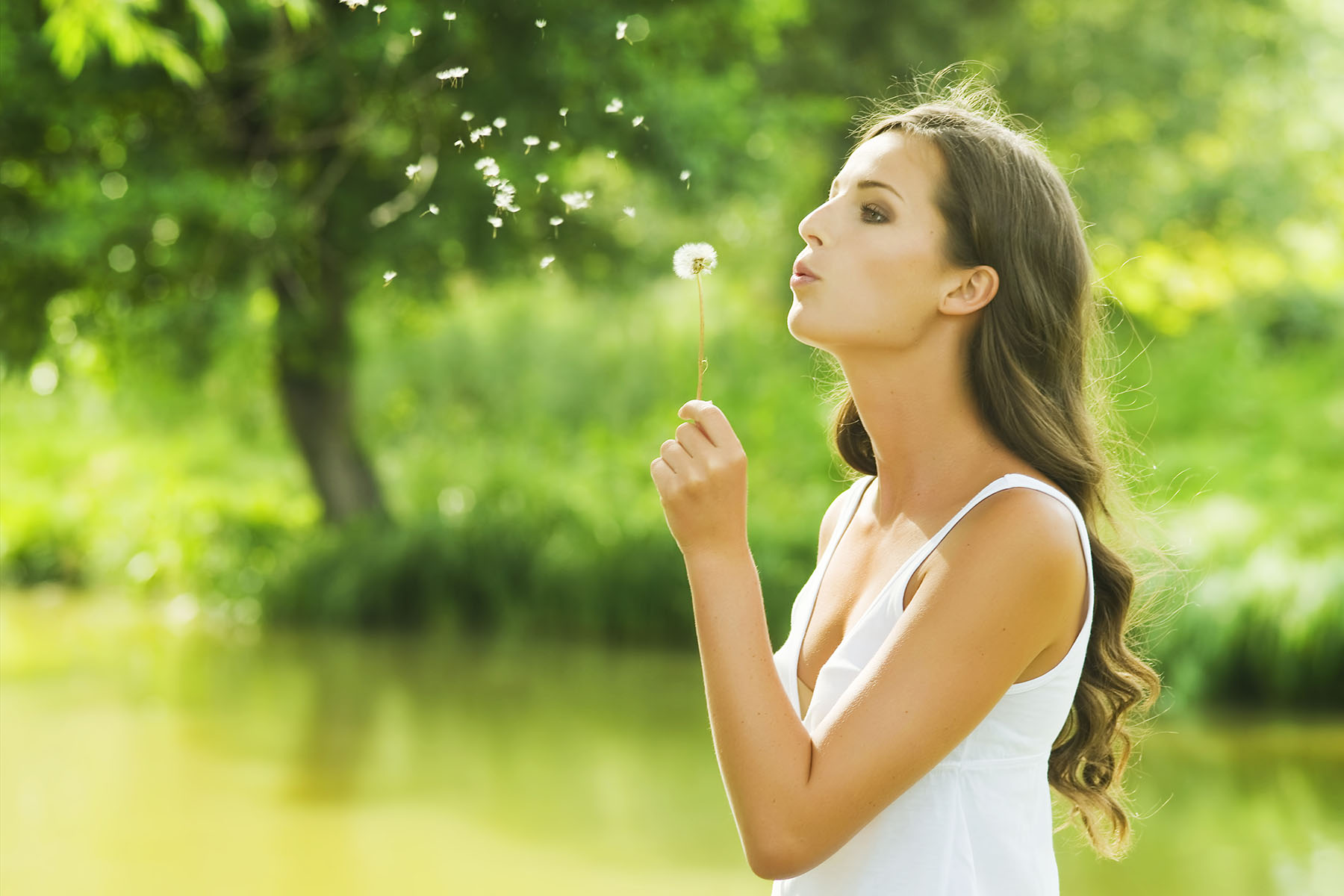 A young woman blowing a dandelion