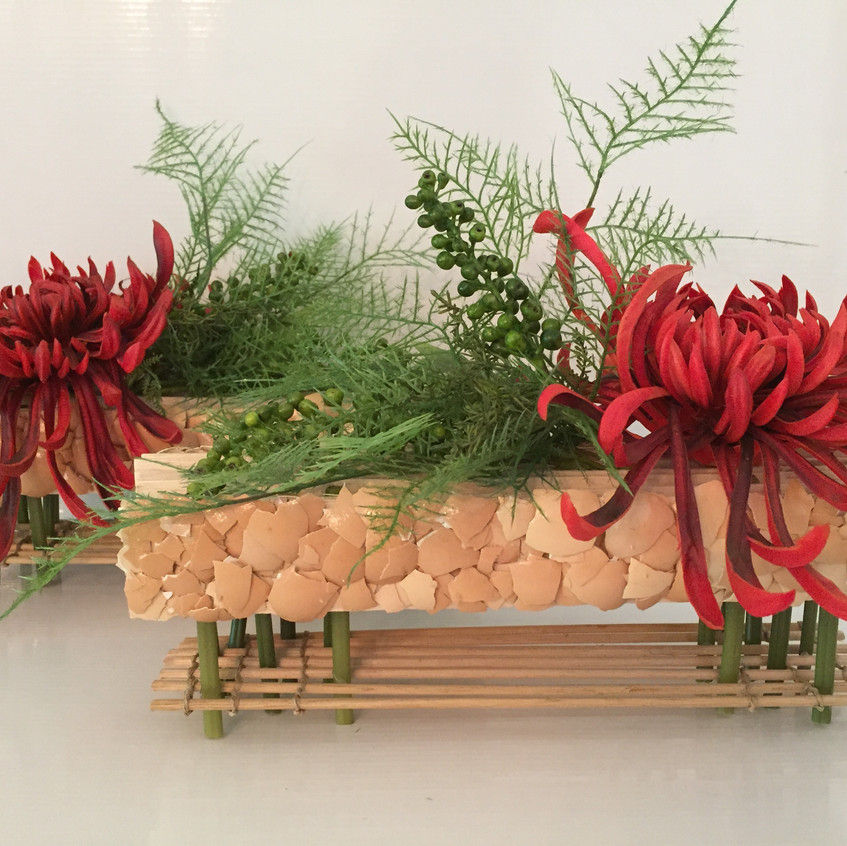 Contemporary floral design on hand made structure with egg shell feature and tatami with faux / artificial flowers including fuji mum, berries and fern