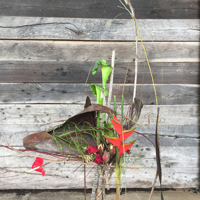 Floral Design with hand made structure (inspiration cow paddock) and fresh flowers including goddess lilies and tropical heliconia