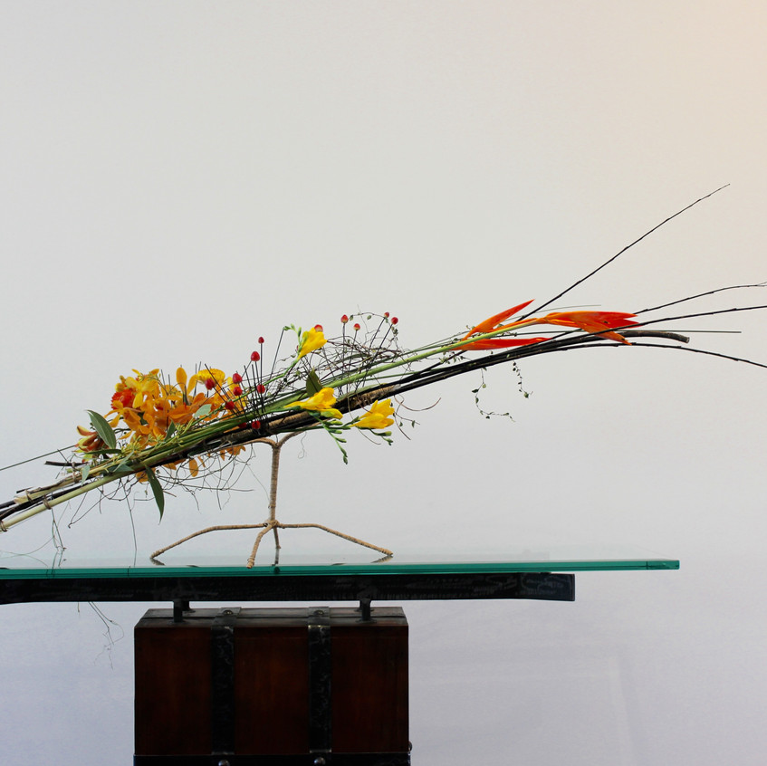 Floral design on hand crafted structure of wire with fresh flowers including vanda orchids, freesias, hypericum berries
