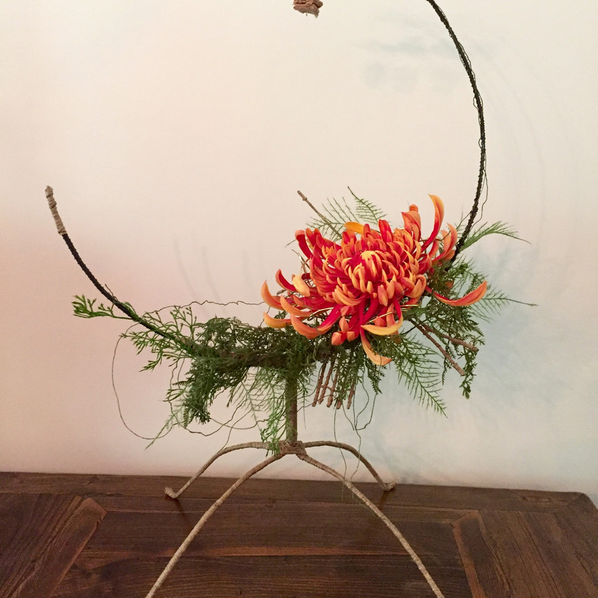 Contemporary floral design on hand crafted structure of wire with faux / artificial flowers including fuji mum, fern and hanging  greenery