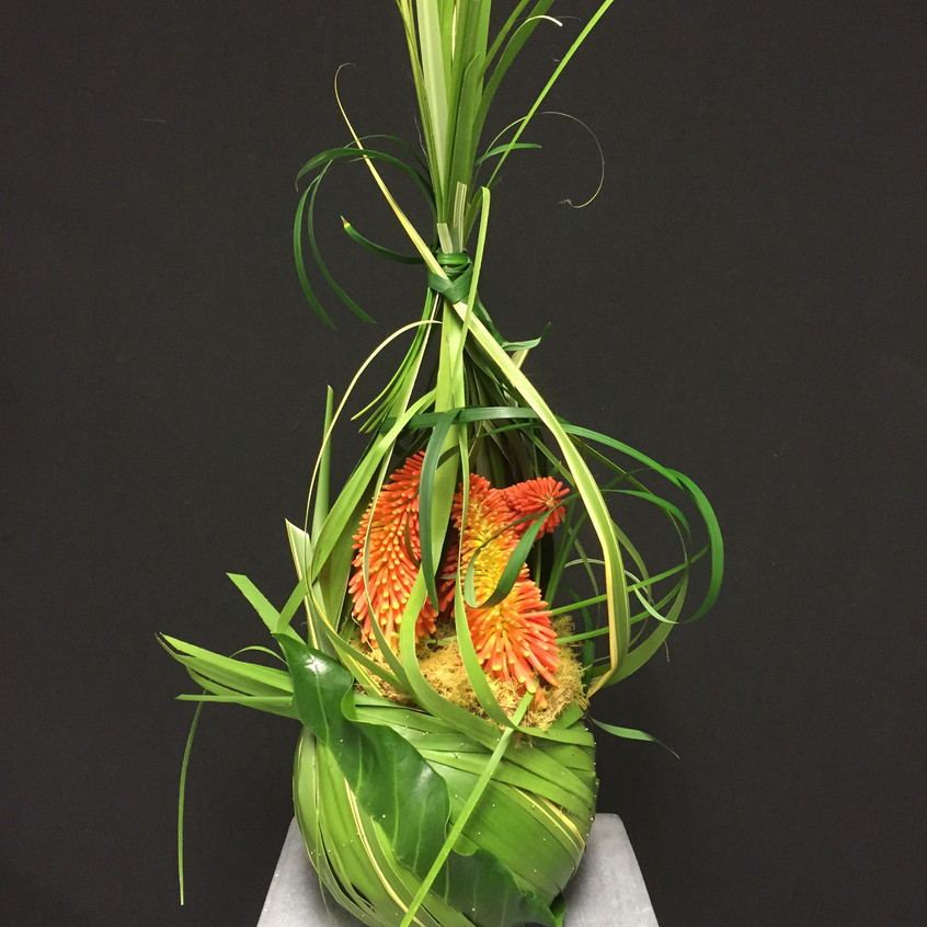 Contemporary floral design including pinned leaves with fresh flowers
