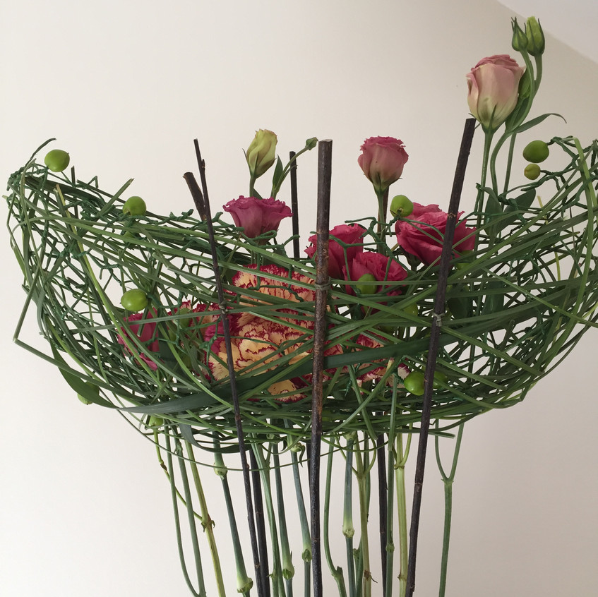 Floral design on hand made  chicken wire structure with fresh flowers including carnations, lisianthus and hypericum berries