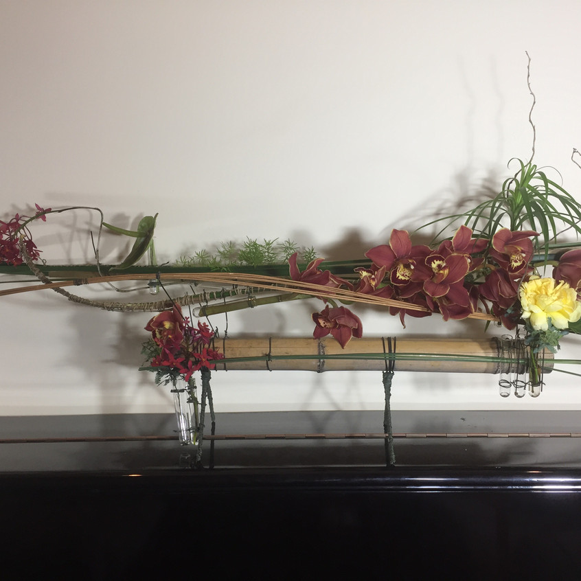 Floral design on hand made structure of bamboo with cymbidium orchids, and carnation