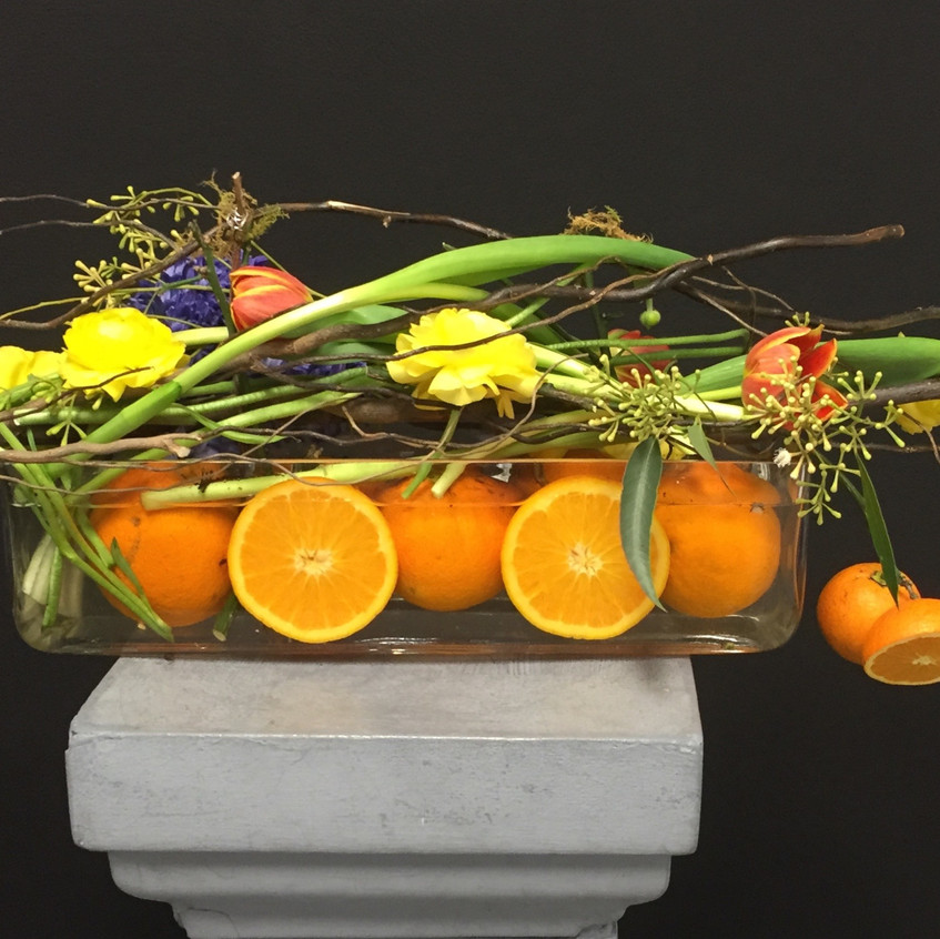 contemporary floral design with hand made structure of branches and fruit including oranges and fresh flowers tulips and hyacinth