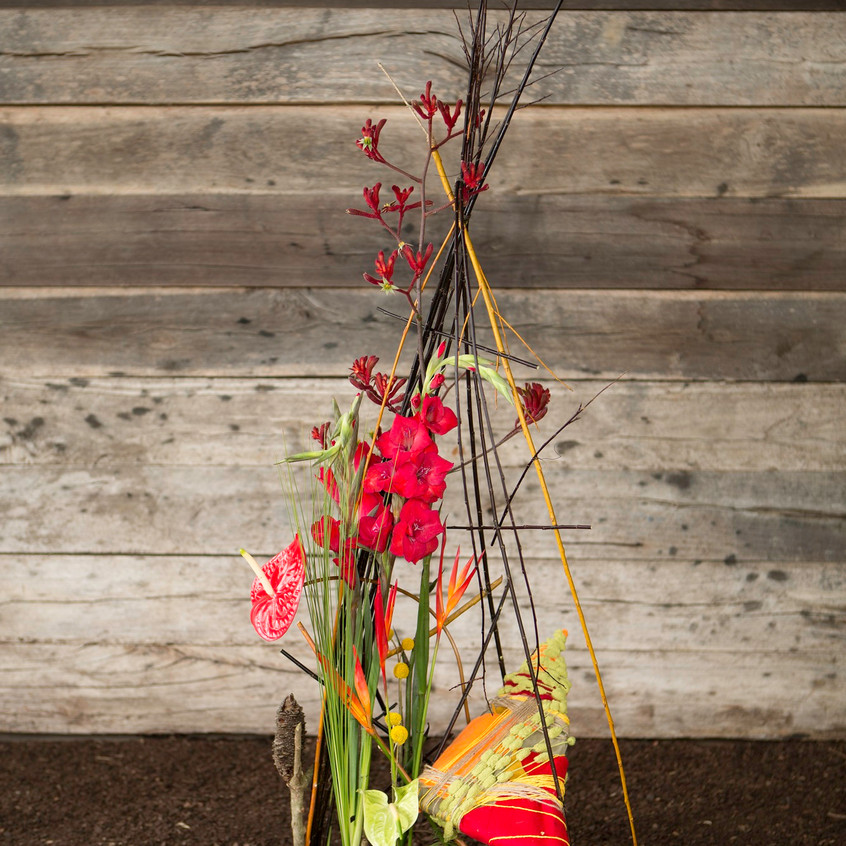 Floral design with hand made structure made with sticks and colour pillow with complimenting colours of red gladiolus and kangaroo paw