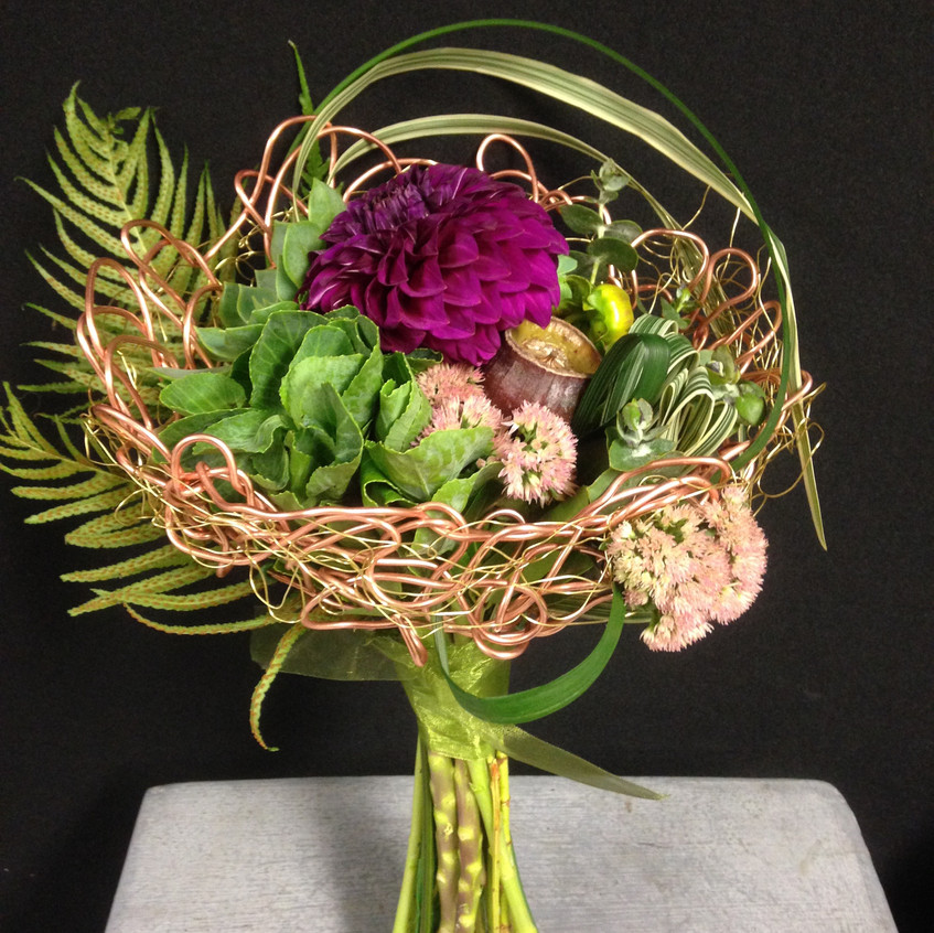 Contemporary floral design with hand crochet wire frame and fresh flowers including dahlia, gum nuts and sedum succulent