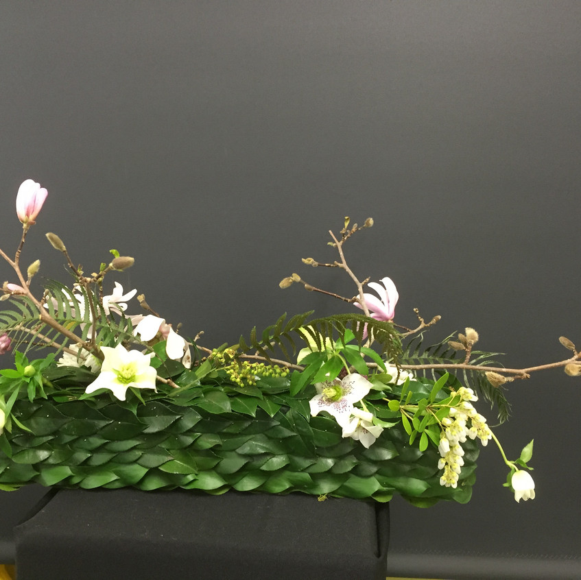 contemporary floral design with pinned leaves and fresh flowers including deciduous magnolia brach tree