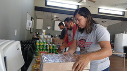 Pastor Chuy, his wife Myrna, and son Jesús helping prepare bags