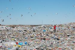 a man walks through trash at dump