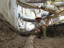 Archaeologist pauses at 19-20th century ceramic sewer pipe unearthed at the Governors mansion Austin